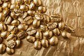 foto of coffee crop  - Golden coffee beans on golden background in studio - JPG