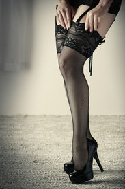 stock photo of fishnet stockings  - Beautiful voluptuous and sexy caucasian adult woman in black fishnet stockings and garters in a boudoir setting lit from the side with window light - JPG