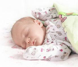 stock photo of sleeping baby  - Closeup color photo of a beautiful newborn baby sleeping peacefully - JPG