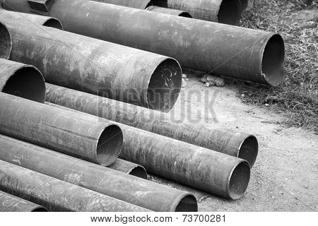 Rusted Industrial Steel Pipes Lay On Ground, Monochrome Photo