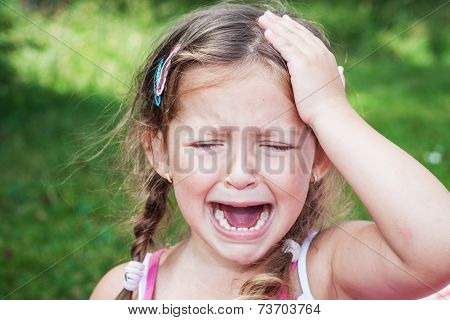 young girl crying because of headache