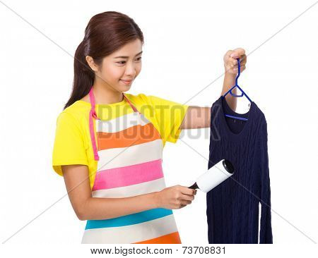 Housewife use dust roller romover on knitwear
