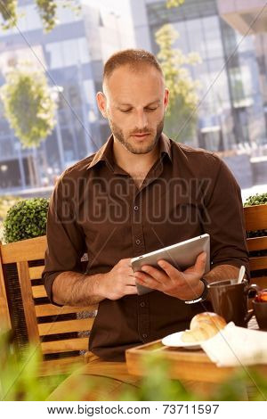 Young man using tablet computer outdoors, sitting on a bench, having breakfast in outdoor coffee.
