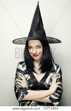 Funny Witch. Young happy woman with carnival hat. Studio shot.