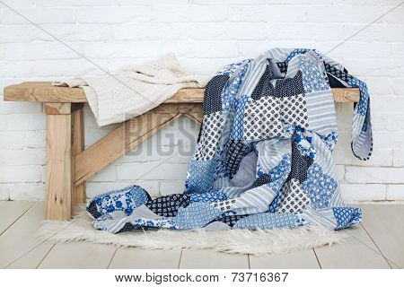 Wooden rustic bench with warm cozy bedding on it