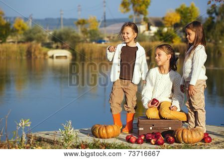 Three cheerful little girls playing on the lake in warm autumn day / Fall lifestyle portrait of children having fun on wooden berth over the river landscape