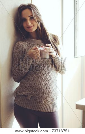 Home cozy portrait of pregnant woman wearing warm cashmere sweater resting at home