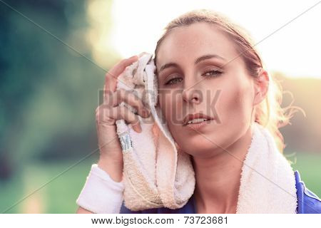 Woman Wiping Face With Towel After Exercise