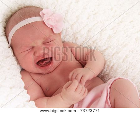 One week old newborn baby girl crying loudly.
