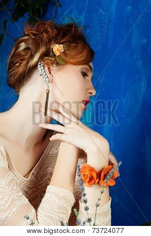portrait of a beautiful woman with red hair in braided hairstyle and flowers in her hair. wearing leather orange bracelet grunge painted background
