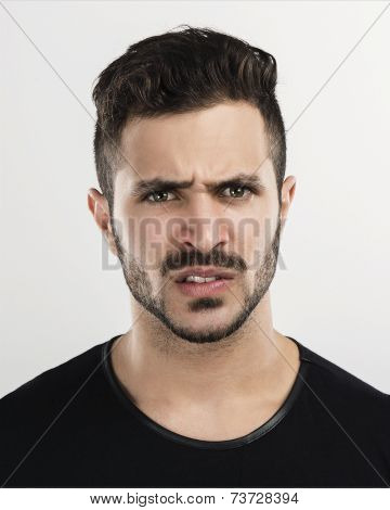 Studio portrait of a handsome young man astonished with a upset expression