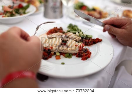 Person Eating Grilled Fish