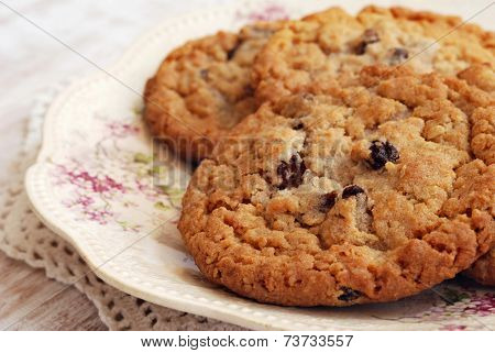 Freshly baked oatmeal raisin cookies on antique plate with distressed wood as background.  Macro with shallow dof.