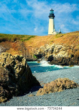 Yaquina Head Light House on a Cliff with blue cloudy sky
