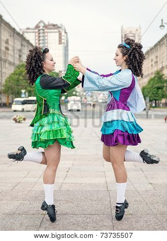 Two Women In Irish Dance Dresses Dancing