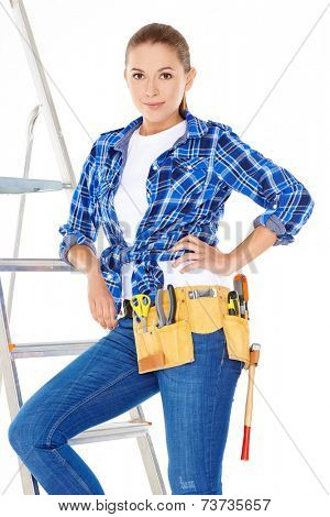 Pretty Young Carpenter Woman in Blue Checkered Polo and Jeans with Tools on Waist Posing at Steel Ladder. Isolated on White Background.