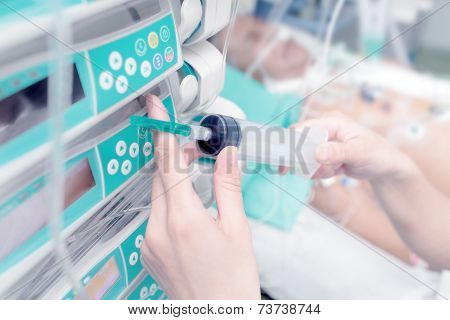 Syringe In The Hand Of A Nurse On The Background Of The Patient In The Icu.