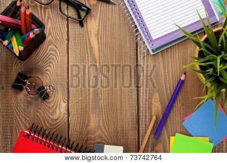 Office table with notepad, colorful pencils, supplies and flower. View from above with copy space