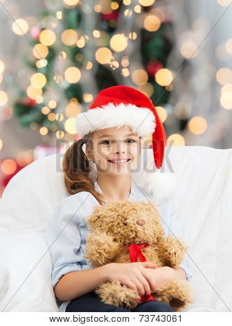 holidays, presents, childhood and people concept - smiling little girl with teddy bear toy over living room and christmas tree background