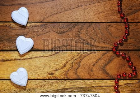 Three White Hearts Misaligned And Wood Background With Necklace