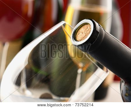 closeup of a bottle with a cork, bottles and glasses on the background