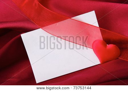 Invitation card on red silk satin background.