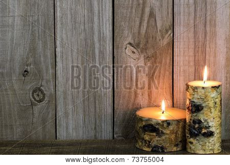 Log candles burning by weathered wooden background