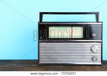 Old radio set on wooden table on blue background