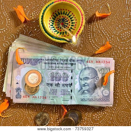 100 rupee bank notes and coins with indian traditional lamp. Bird eye view.