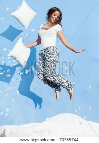Happy morning concept, woman holding a pillow jumping up on bed