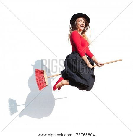 Young attractive woman wearing witch fancy dress flying on a broom, halloween concept