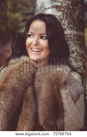 Beautiful brunette woman standing in a park near a tree