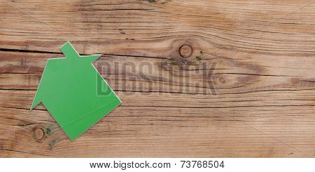 House shaped sign on rustic wood background
