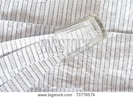 Glass on a printout of DNA sequence,  stripes of DNA sequences inside