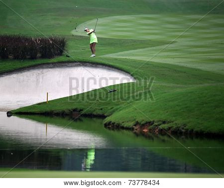 KUALA LUMPUR, MALAYSIA - OCTOBER 10, 2014: Brittany Lang of the USA makes a shot across the lake at the 18th hole of the KL Golf & Country Club at the 2014 Sime Darby LPGA Malaysia golf tournament.