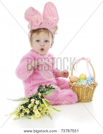 An adorable baby girl attempting to whistle in her fluffy pink Easter bunny outfit.  She sits beside a basket of colored eggs and a small bouquet of yellow flowers.  On a white background.