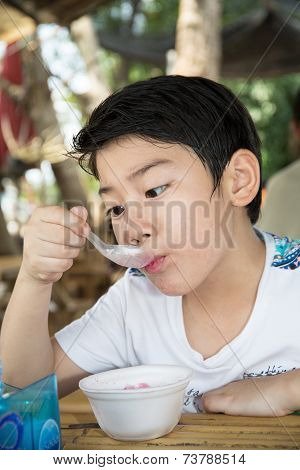 Little Asian Child Enjoy Eating An Red Ice Cream