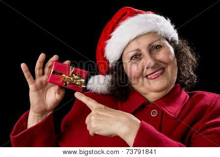 Joyful Aged Lady Pointing At Red Christmas Gift.