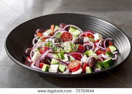 Greek salad in black bowl, over dark slate.