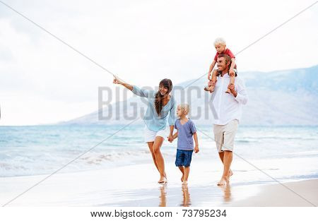 Happy Young Family Walking Down the Beach at Sunset