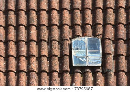 Old Broken Dormer Window In The Red Tiled Roof