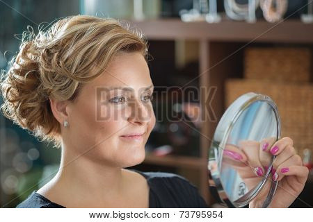 Beautiful young woman looking into a mirror