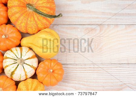 High angle still life of autumn decorative pumpkins and gourds. Horizontal format on a white wood table with copy space.