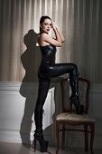 image of catsuit  - Sexy woman in latex catsuit step on chair - JPG