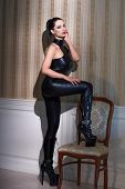 picture of catsuit  - Sexy woman in latex catsuit steps on chair at vintage wall desire - JPG