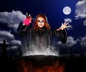 foto of witches cauldron  - Young witch with red potion and cauldron on night sky background - JPG