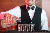 stock photo of bartender  - Bartender is making cocktail at bar counter