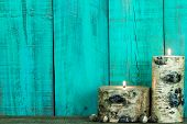 stock photo of quaint  - Textured log candles lit by antique teal blue rustic wall - JPG