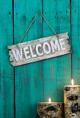 pic of log fence  - Wood welcome sign by burning log candles hanging on antique green distressed background - JPG