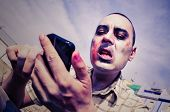picture of walking dead  - a scary zombie using a smartphone - JPG